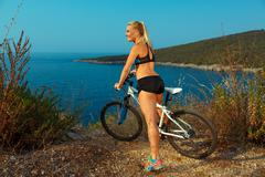 Woman cyclist on a mountain bike looking at the landscape of mountains and se Stock Photos