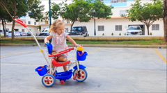 Stock Video Footage of Little Blond Girl Pushes Pram Tricycle about Play Ground