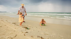 Grandfather Comes to Small Boy Girl on Wet Beach Sand Wave Surf Stock Footage