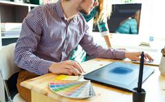 Artist drawing something on graphic tablet at the home office - stock photo