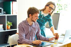 Young woman and man working from home - modern business concept - stock photo