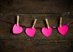 Pink heart paper cut out with clothes pins - stock photo