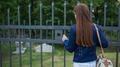 Woman observing over iron fence of Jewish cemetery Stock Footage