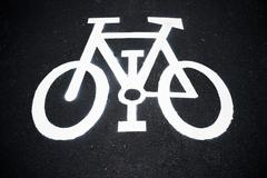 Bike lane sign painted on a street Stock Photos