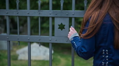 Person hold to fence with Jewish star close up Stock Footage
