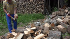 Strong worker man chop firewood on log, leave axe and walk away. 4K Stock Footage