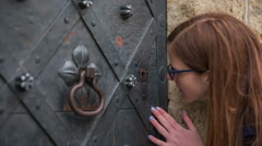 Woman peeping through iron keyhole Stock Footage