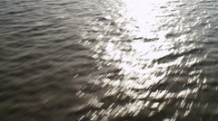 Low flight over sun glare on rushing water. Shot in 2011. Stock Footage