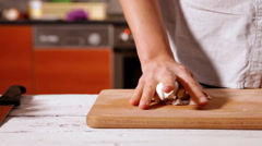 Woman crushed the garlic head with hand on the wooden cutting board Stock Footage