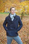 Happy young man smiling outdoors in fall season - stock photo