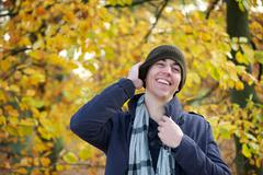 Young man laughing outdoors on an autumn day - stock photo