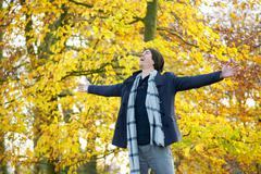 Carefree young man standing outdoors with open arms - stock photo