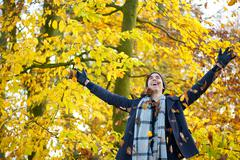 Happy young man smiling and throwing leaves with open arms - stock photo
