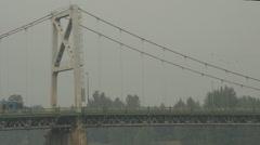 Suspension bridge, transport trucks lowboy and excavator, long shot Stock Footage