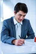 Smiling asian businessman read a estate contract - stock photo