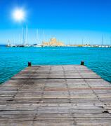 wooden batten bridge juts out into the expanse of the sea - stock photo