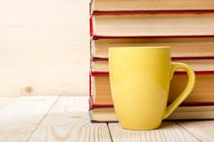 Stack of colorful books and cup on wooden table. Back to school. Copy space Stock Photos