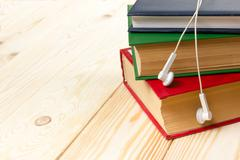 Stack of colorful books on wooden table and headphones. Audiobook concept Stock Photos