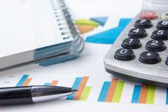 Finance concept - Financial accounting stock market graphs analysis. Calculator Stock Photos