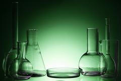 Assorted empty laboratory glassware, test-tubes. Green tone medical background - stock photo