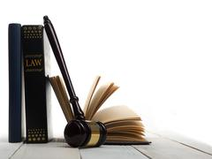 Open law book with wooden judges gavel on table in a courtroom Stock Photos