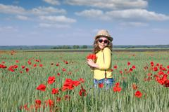 Happy little girl with poppy flower spring season Stock Photos