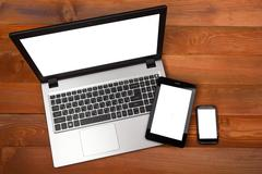 Set of modern gadgets includes laptop, digital tablet and smartphone with empty - stock photo