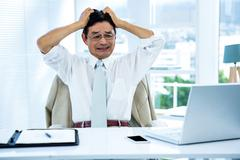 Overwhelmed asian businessman going crazy - stock photo