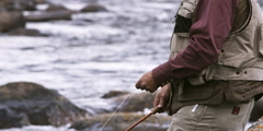 Senior fly fisherman casting into a river in Wyoming Stock Footage
