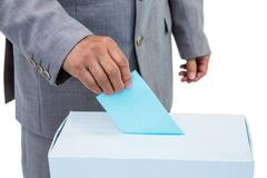 Stock Photo of Businessman putting ballot in vote box