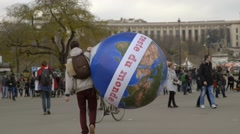 Protester carrying large inflatable earth meets demonstrator, COP21 Stock Footage