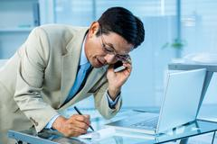 Overwhelmed asian businessman answering the phone and writing - stock photo