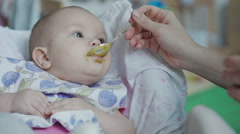 Mother feeding baby food to baby Stock Footage