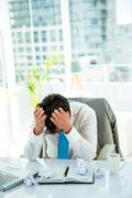 Stressed businessman with head in hands Stock Photos