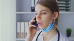 The young nurse speaks by phone with the patient Stock Footage