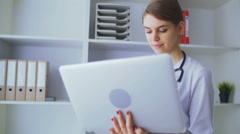 The young nurse works behind the laptop Stock Footage