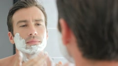 Adult man shaving with foam and manual razer Stock Footage