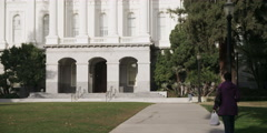 Woman walking away on sidewalk in front of the California State Capitol Stock Footage