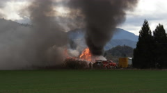 A tower of black smoke and flame rises above a burning structure as firemen turn Arkistovideo