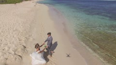 Bride and groom turning around on the beach, aerial drone view - stock footage