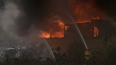 Rubble of a metal roof lies in the left foreground as firefighters shoot streams - stock footage