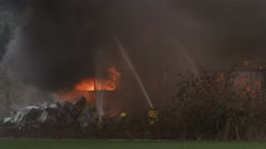Firemen spraying water on a house engulfed in flame Stock Footage