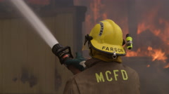 Fireman adjusts the nozzle of a high pressure hose as he sprays a burning Stock Footage