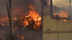 Flames consume charred rubble inside a house destroyed by fire - stock footage