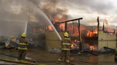 Firemen walking over to stand by a co-worker spraying flames in a burned house Stock Footage