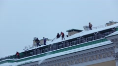Cleaners group on snowy roof, one men use shovel to drop down snow Stock Footage