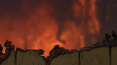 Fire blazes behind the charred wall of a burning house - stock footage
