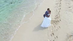 Just-married couple on a caribbean beach, wedding day - drone view - stock footage