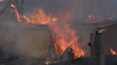 Flames consume collapsed rubble and the remaining portion of a wall in a house - stock footage