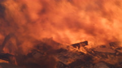 Flames raging above the collapsed wall of a burning house fill the frame - stock footage